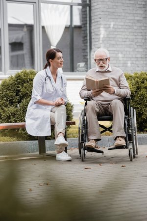 Photo for Handicapped aged man reading book in wheelchair near social worker sitting on bench on blurred foreground - Royalty Free Image