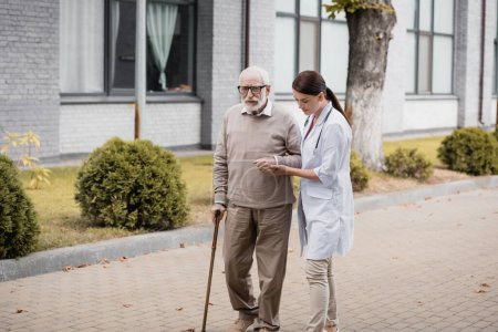 social worker supporting man with walking stick while strolling together outside