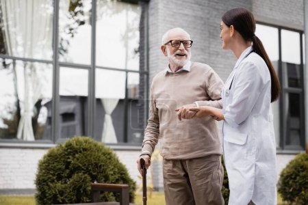 geriatric nurse supporting aged man strolling with walking stick