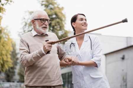 aged man pointing with walking stick away near smiling geriatric nurse