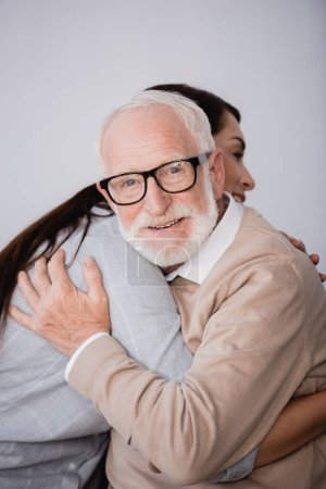smiling aged man looking at camera while hugging adult daughter at home