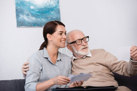 Photo for Happy woman with aged father looking at family photos together - Royalty Free Image