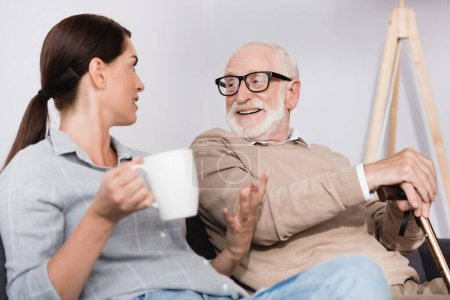 Photo for Brunette woman holding tea and gesturing while talking to cheerful elderly father - Royalty Free Image