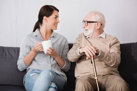 brunette woman with cup of tea and smiling aged man with walking stick talking while sitting on sofa at home