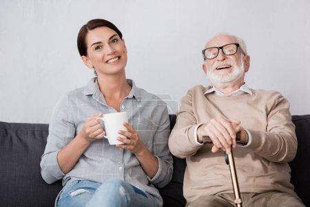 Photo pour Femme gaie et rire père âgé regardant la caméra tout en étant assis sur le canapé - image libre de droit