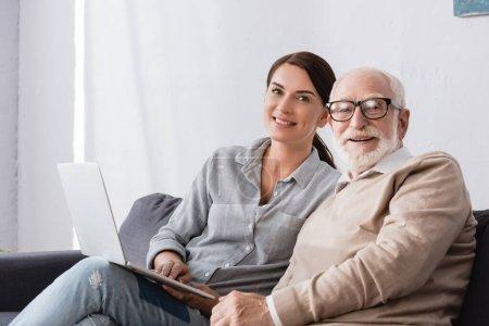 Photo pour Femme brune souriante regardant la caméra tout en étant assis près du père âgé et en utilisant un ordinateur portable - image libre de droit