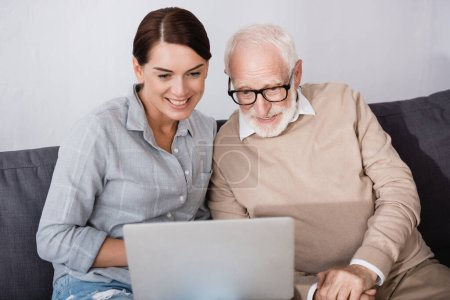 smiling woman with concentrated father using laptop together at home