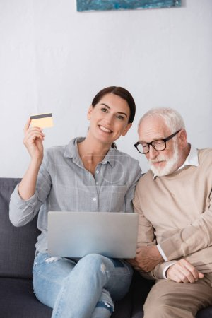 cheerful woman holding laptop and credit card while sitting near elderly father