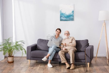 Photo for Aged man with adult daughter sitting on sofa at home with laptop and credit card - Royalty Free Image