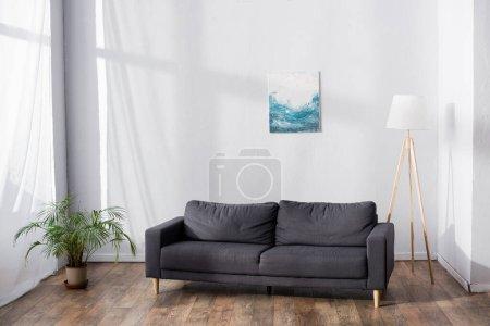 weiches bequemes Sofa im Wohnzimmer in der Nähe von Topfpflanzen