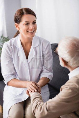 Photo pour Infirmière souriante tenant la main d'un homme âgé assis sur le canapé à la maison - image libre de droit