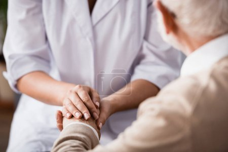 cropped view of social worker holding hands of aged man on blurred background