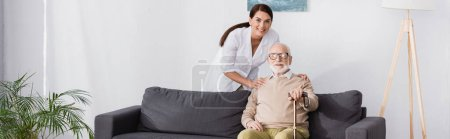 geriatric nurse and aged man smiling at camera together at home, banner