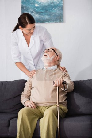 Photo for Smiling elderly man sitting on sofa with walking stick and looking at social worker - Royalty Free Image