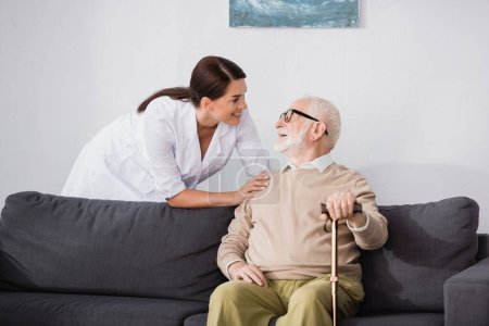 smiling geriatric nurse talking to elderly man sitting on sofa at home