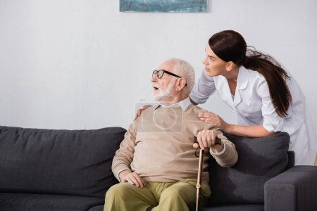 Photo for Aged man looking away while sitting on sofa near social worker - Royalty Free Image