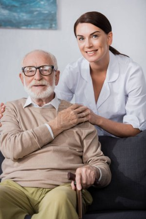 social worker holding hands and embracing aged man while looking at camera