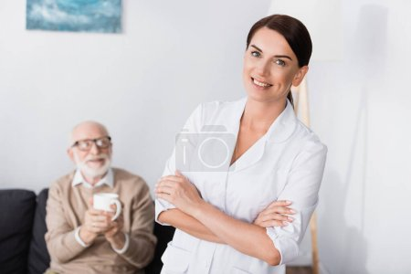 Photo pour Travailleur social joyeux souriant à la caméra tout en se tenant avec les bras croisés près de l'homme âgé tenant une tasse de thé - image libre de droit