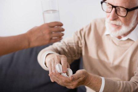 anciano en anteojos tomando pastillas cerca de la enfermera dando vaso de agua en primer plano borrosa