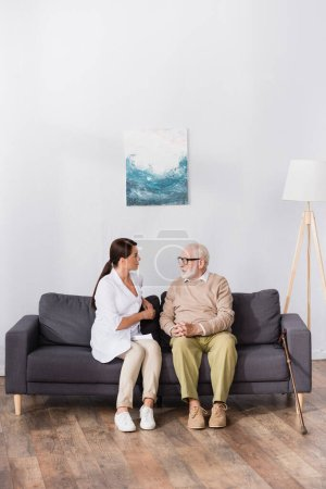 aged man in eyeglasses talking to geriatric nurse while sitting on sofa at home