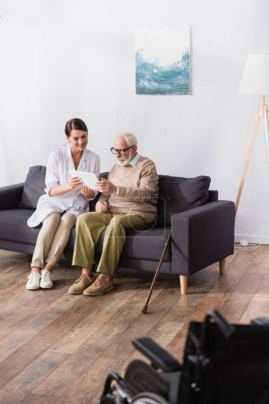smiling social worker showing digital tablet to concentrated elderly man