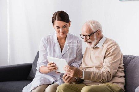 brunette social worker showing digital tablet to smiling aged man at home