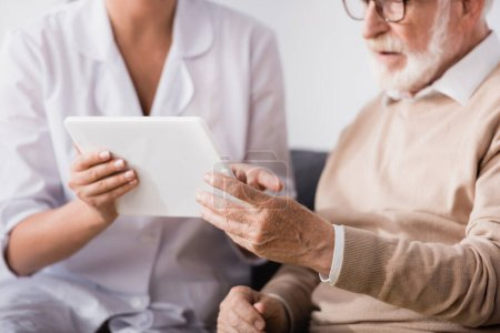 cropped of social worker showing digital tablet to aged man at home