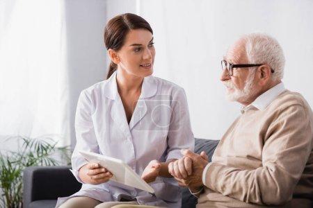Photo pour Travailleur social tenant tablette numérique et parlant à un homme âgé assis avec les mains serrées - image libre de droit