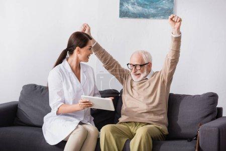 social worker holding digital tablet near excited aged man showing winner gesture