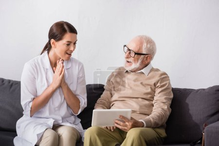 brunette social worker showing wow gesture while looking at aged man holding digital tablet