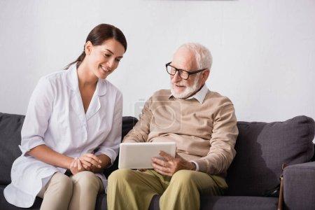 smiling aged man using digital tablet near cheerful geriatric nurse at home