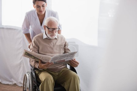geriatric nurse near elderly handicapped man reading newspaper in wheelchair