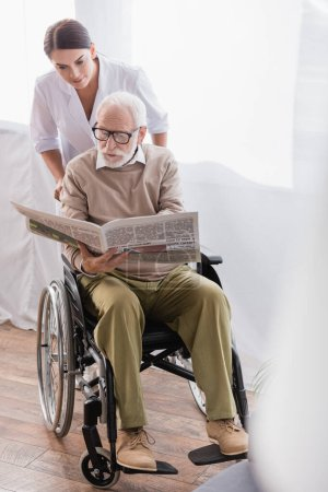 aged disabled man reading newspaper in wheelchair near social worker