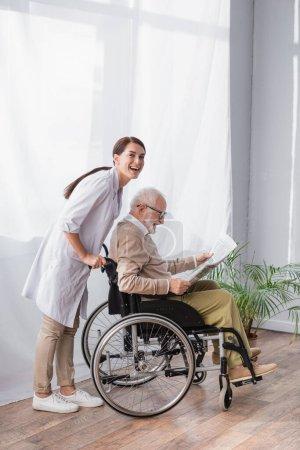 geriatric nurse smiling at camera near disabled elderly man reading newspaper in wheelchair