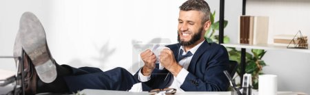 Stressed businessman holding clumped paper near table in office, banner