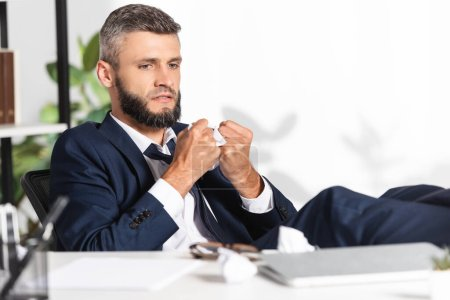 Photo for Stressed businessman holding clumped paper near laptop and stationery on blurred foreground in office - Royalty Free Image