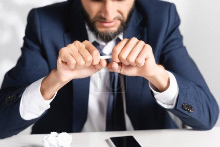 Photo for Cropped view of stressed businessman holding pencil near clumped paper and smartphone in office - Royalty Free Image