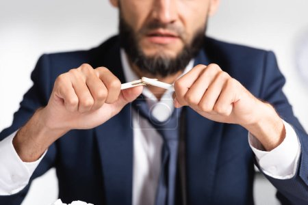 Photo for Broken pencil in hands of stressed businessman on blurred background - Royalty Free Image