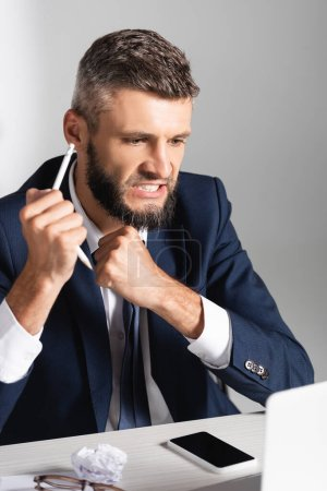Photo for Tensed businessman holding broken pencil near smartphone, clumped paper and eyeglasses on blurred foreground - Royalty Free Image