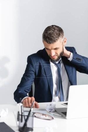Businessman touching neck near laptop and stationery on blurred foreground in office