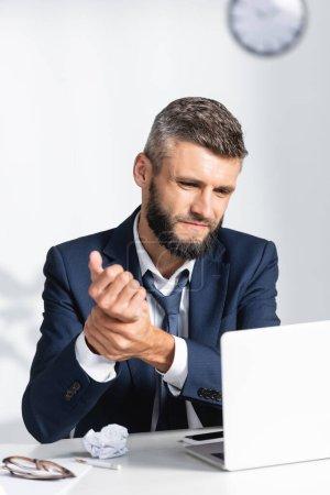 Geschäftsmann berührt Arm, während er unter Schmerzen in der Nähe von Gadgets auf Arbeitstisch im verschwommenen Vordergrund im Büro leidet
