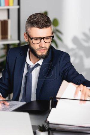 Photo pour Homme d'affaires tenant des papiers tout en travaillant à table sur le premier plan flou - image libre de droit