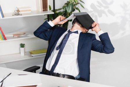 Foto de Empresario cubriendo la cara con la carpeta de papel cerca de la mesa en primer plano borroso en la oficina - Imagen libre de derechos