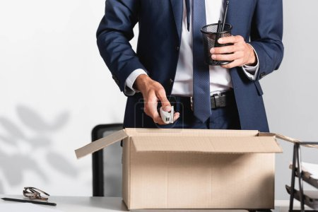 Photo for Cropped view of fired businessman holding stationery near carton box on table in office - Royalty Free Image