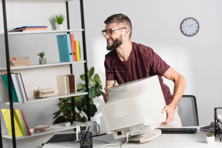 Angry businessman holding computer monitor during nervous breakdown in office
