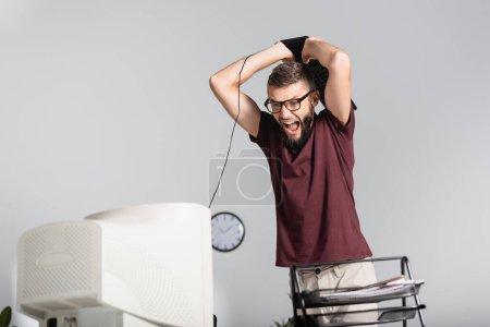 Schreiender Geschäftsmann mit Tastatur neben Computermonitor und Papieren im verschwommenen Vordergrund im Büro