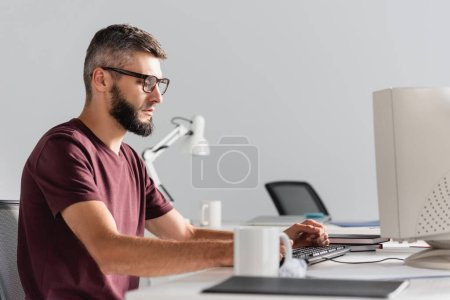 Businessman in casual wear using computer near stationery on blurred foreground in office