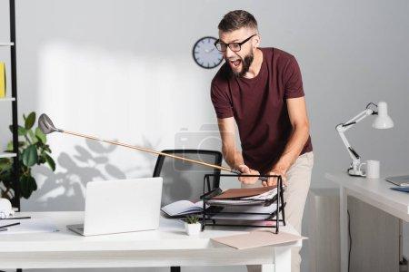 Wütender und schreiender Geschäftsmann hält Golfschläger in der Nähe von Dokumenten und Laptop im Büro