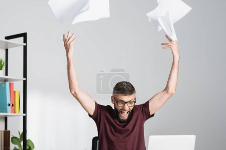 Tensed and screaming businessman throwing documents near laptop on blurred foreground in office