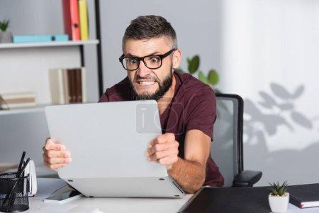 Photo pour Homme d'affaires fou tenant un ordinateur portable près du dossier papiers sur le premier plan flou dans le bureau - image libre de droit